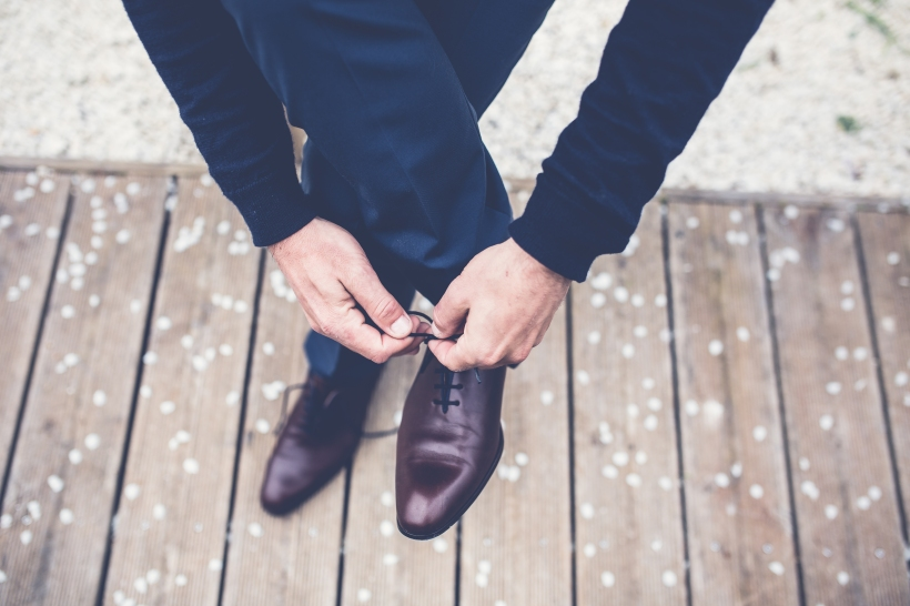 man tying his dress shoes