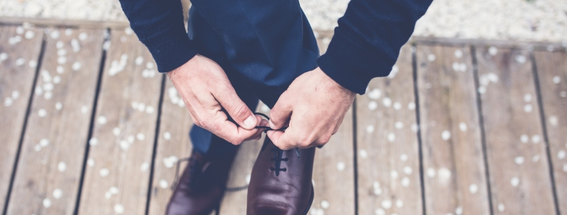 man tying his dress shoes