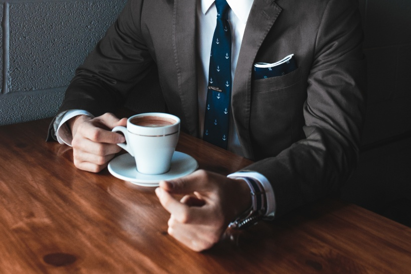 man in a suit having coffee