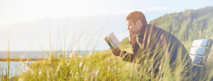man reading in a field